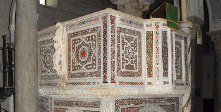A large, freestanding pulpit carved from marble and decorated with sculptures and mosaics